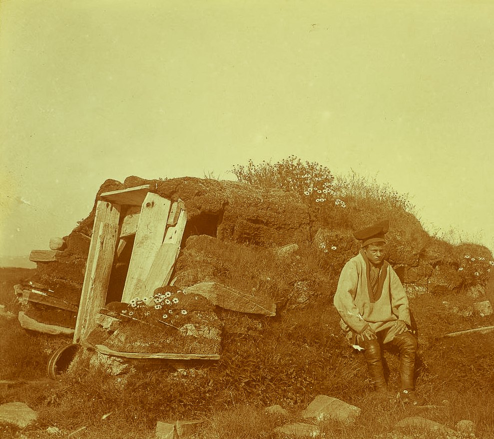 A Sami man sitting in front of a well at Tamsøya, an island on the coast of Finnmark, Norway. Possibly taken in 1903. | Photo: Robert Collett - nb.no - Public domain.