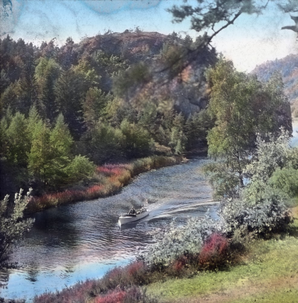 A boat on the canal. A beautiful and tranquil setting near the south coast. Reddalskanalen, Grimstad, Agder, Norway. Hand-coloured photo. | Photo: Anders Beer Wilse - digitaltmuseum.no DEX_W_00541 - cc by.