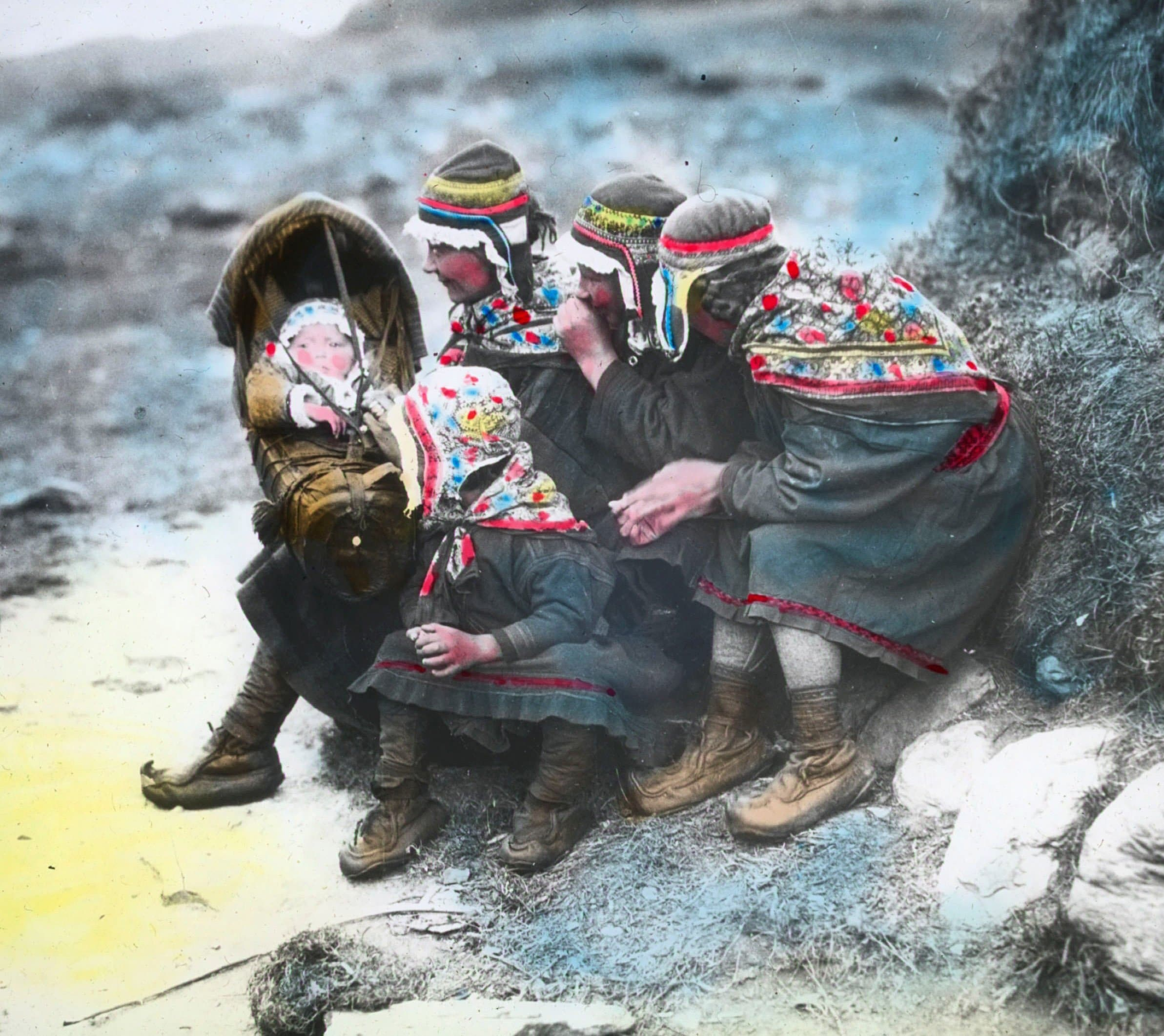 Group of Sami women and children - probably from the Swedish side of the border. The baby is strapped in a so-called «komse», carried on the mother's back when walking. Finnmark, Norway. Hand-coloured photo. | Photo: Alf Schrøder co - digitaltmuseum.no FBib.01005-056 - Public domain.