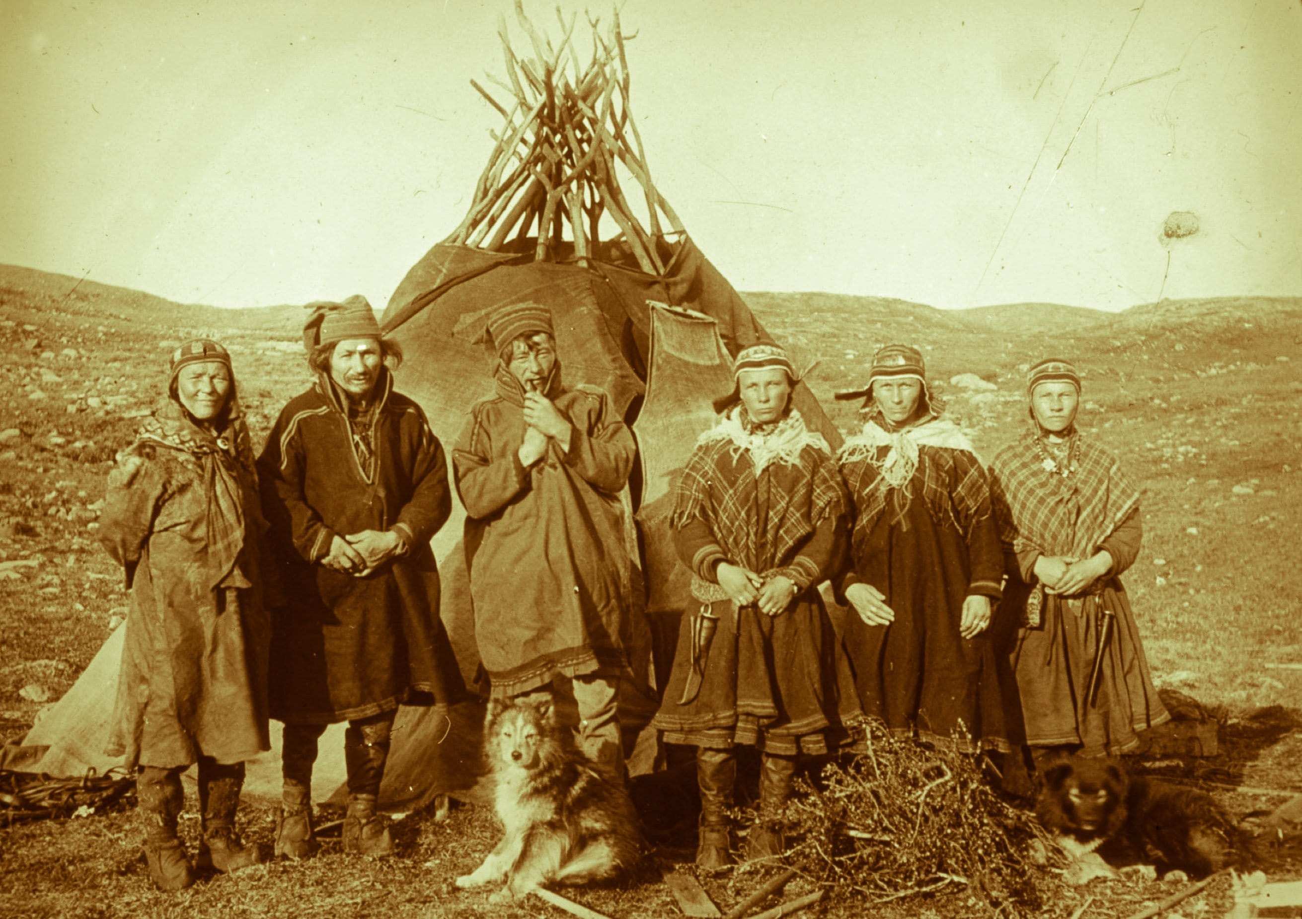 Henrik Sara, his wife, two daughters and a third girl outside their tent. Mikkel Bonga with the pipe. Cedar's mine, Badderen, Kvænangen, Finnmark, Norway. | Photo: Hanna Resvoll-Holmsen - digitaltmuseum.no FBib.01005-070 - Public domain.