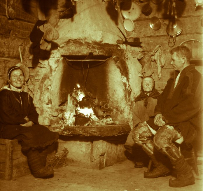 Sami family around the fire in a log cabin. Finnmark, Norway. | Photo: Alf Schrøder co - digitaltmuseum.no FBib.01005-071 - Public domain.