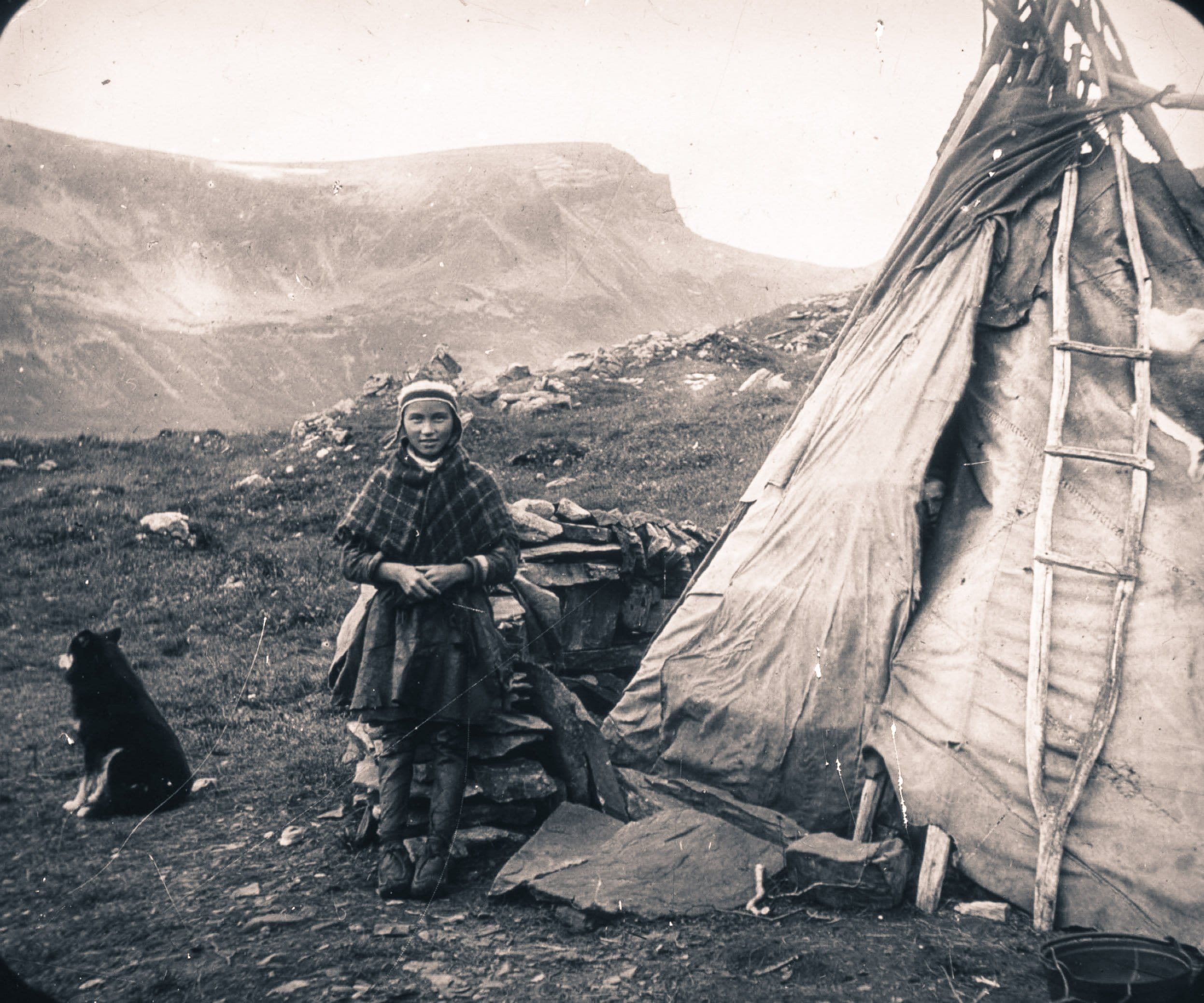 Young Sami girl outside a tent. Troms, Norway. | Photo: Hanna Resvoll-Holmsen - digitaltmuseum.no FBib.01006-016 - Public domain.