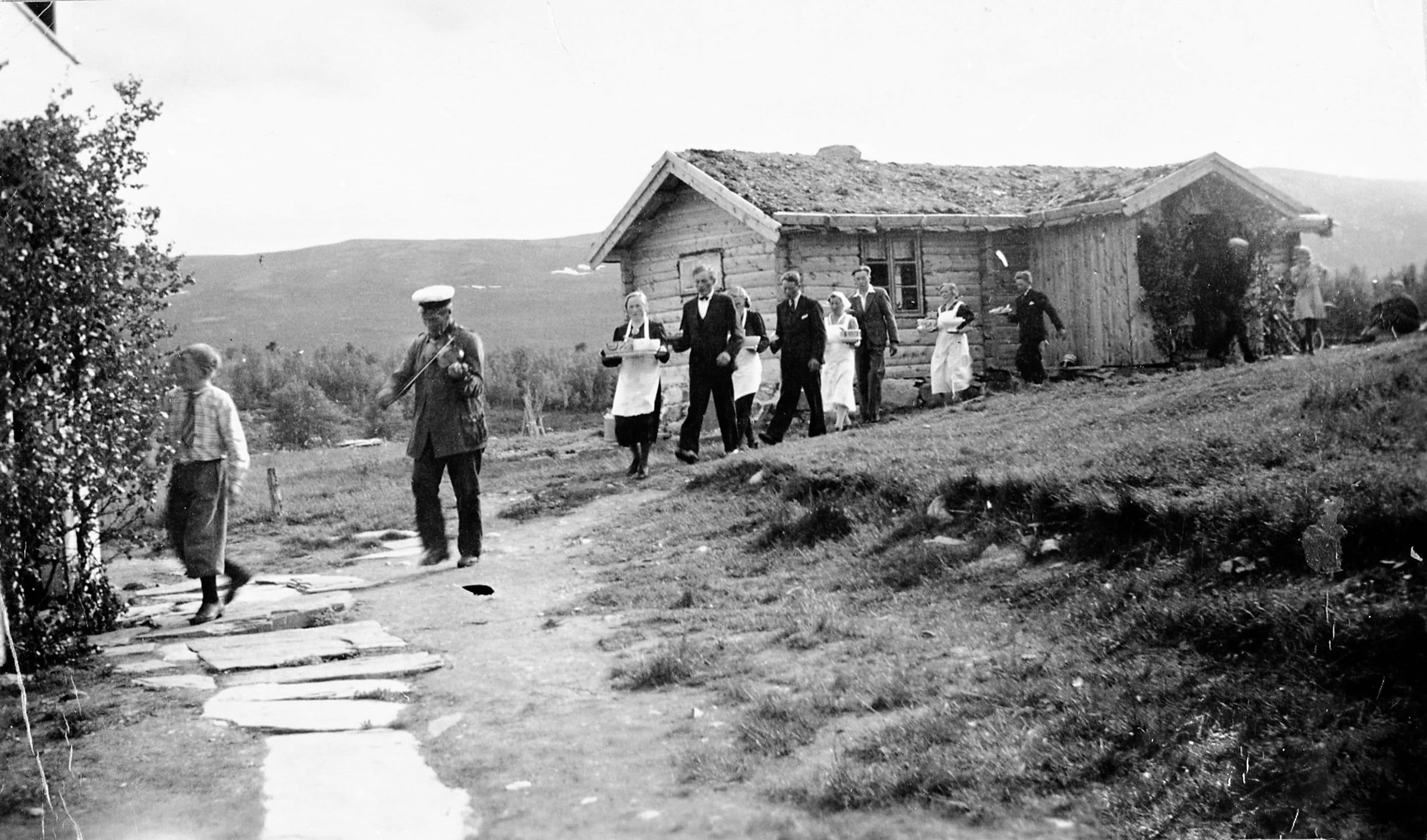 A wedding at Kvilvang Nordre farm, Tufsingdalen, Os, Hedmark, Norway. The fiddler is leading the procession - as the porridge is brought in to hungry guests. Taken prior to 1928. | Photo: Peder J. Bredalslien - digitaltmuseum.no MINØ.024018 - public domain.