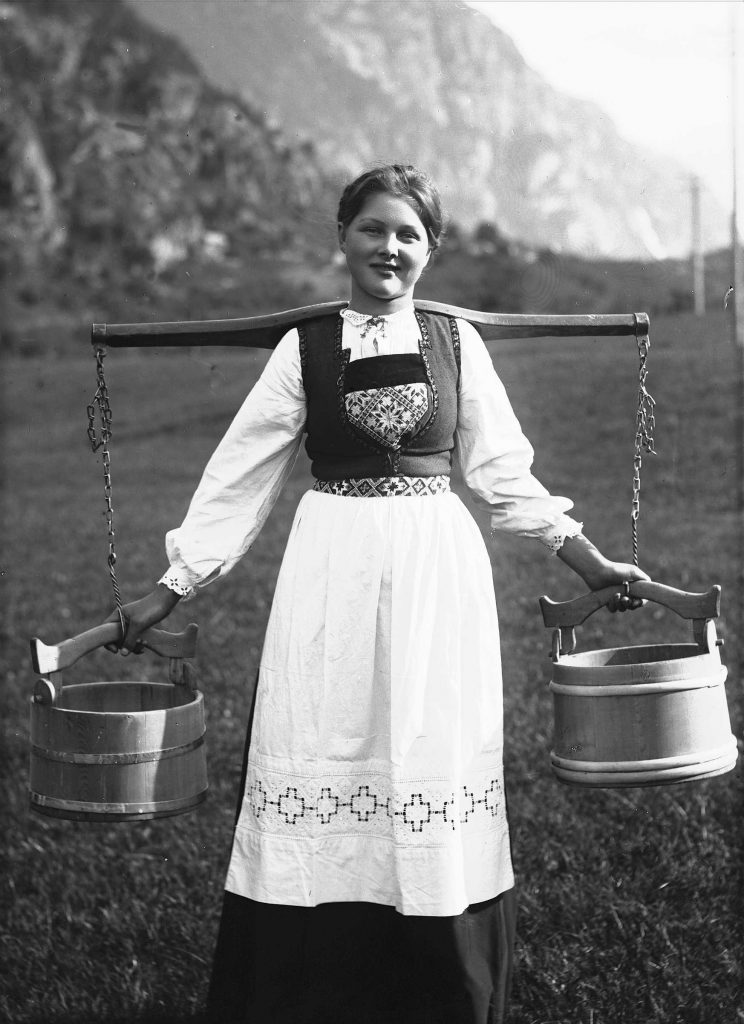 A young girl posing in her folk costume from Hardanger, Hordaland, Norway in 1908. Water yoke and wooden buckets for carrying water. | Photo: Solveig Lund - digitaltmuseum NF.25780-088 - Public domain.