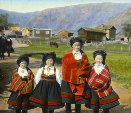 On their way to church. Four girls in their folk costumes from Setesdal. The photo is hand-coloured and taken in 1934 - somewhere in Aust-Agder, Norway. | Photo: Anders Beer Wilse - digitaltmuseum.no DEX_W_00067 - cc by.