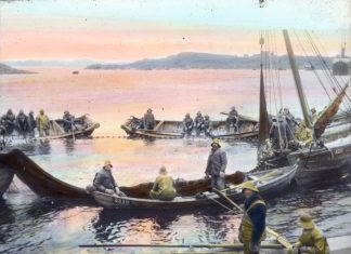 Norwegian fishermen - harvesting the ocean close to the coast. Hand-coloured photo from the beginning of the 1900s. | Photo: Anders Beer Wilse - digitaltmuseum.no DEX_W_00520 - cc by.