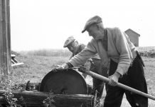 Otto Horndal sharpens his scythe on the old grindstone. The name of the man pulling the crank handle is not known. The location is Horndalen, Elverum, Hedmark, Norway - and the year is 1958. If you ever visit a Norwegian farm, ask to be shown where the grindstone is. A surprisingly large number of farms still have the grindstone tucked away somewhere - or even displayed in a prominent place. For many,it is a symbol of the old farming way of life - evoking childhood memories and emotions. | Photo: Dagfinn Grønoset Glomdalsmuseet - digitaltmuseum.no DGS.2971 - cc by-sa.
