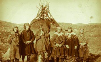 Henrik Sara, his wife, two daughters and a third girl outside their tent. Mikkel Bonga with the pipe. Cedar's mine, Badderen, Kvænangen, Troms, Norway. | Photo: Hanna Resvoll-Holmsen - digitaltmuseum.no FBib.01005-070 - Public domain.