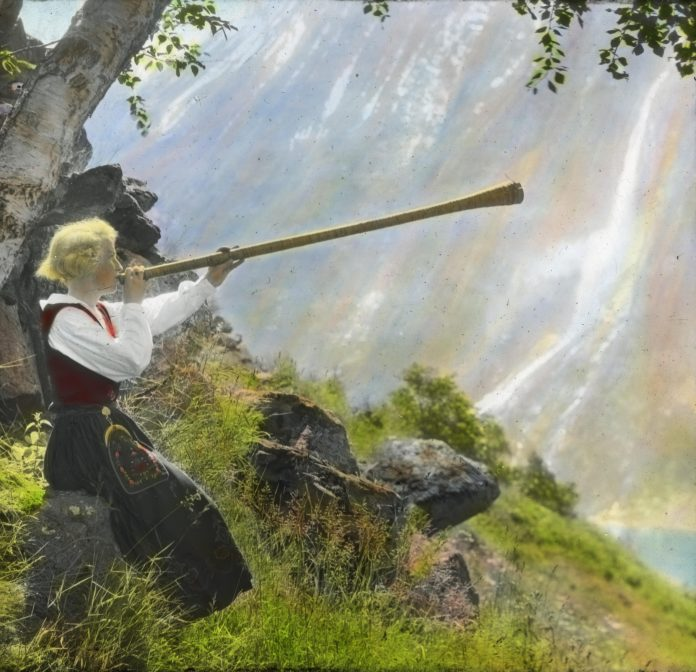 Anna Vinje about to play her «lur» - a shepherd's horn. The location is Geiranger, Stranda, Møre og Romsdal, Norway. Hand-coloured photo taken in 1935.   Photo: Anders Beer Wilse - digitaltmuseum.no DEX_W_00051 - cc by.