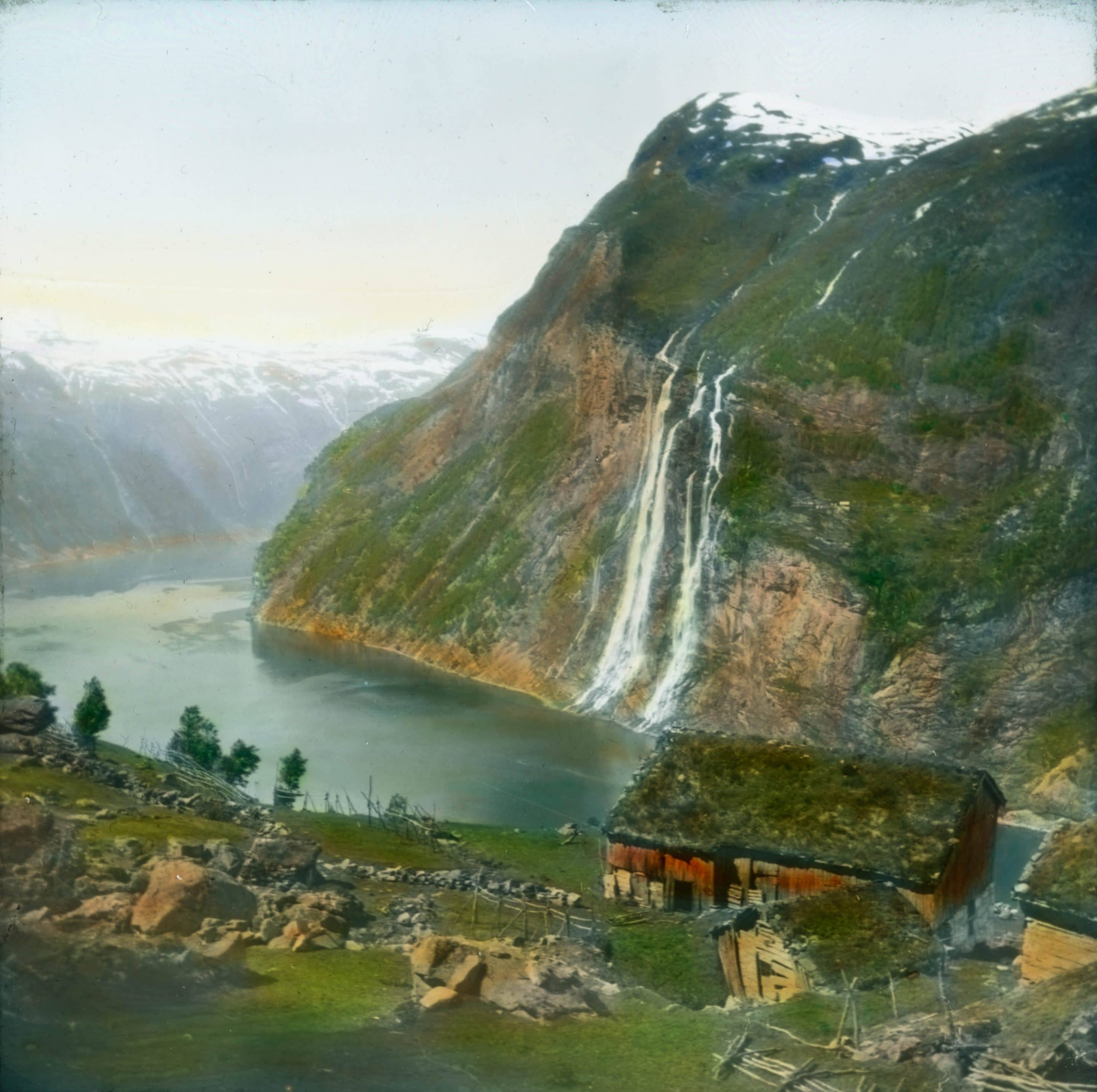 The Seven Sisters waterfall and the Geiranger fjord. A hand-coloured photo from the early 1900s - taken from above the Skagenflå farm, today a tourist attraction - located in Stranda, Møre og Romsdal, Norway. | Photo: Anders Beer Wilse - digitaltmuseum.no DEX_W_00374 - cc by.