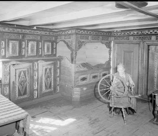 A lady with her spinning wheel.   Photo: Mittet & Co. AS nb.no cc pdm