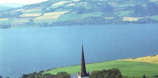 Mjøsa and the Ringsaker church. | Photo: Widerøes Flyveselskap A/S - Anno Domkirkeodden cc pdm.