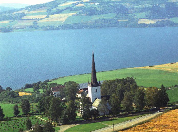 Mjøsa and the Ringsaker church. | Photo: Widerøes Flyveselskap A/S - Anno Domkirkeodden cc pdm.
