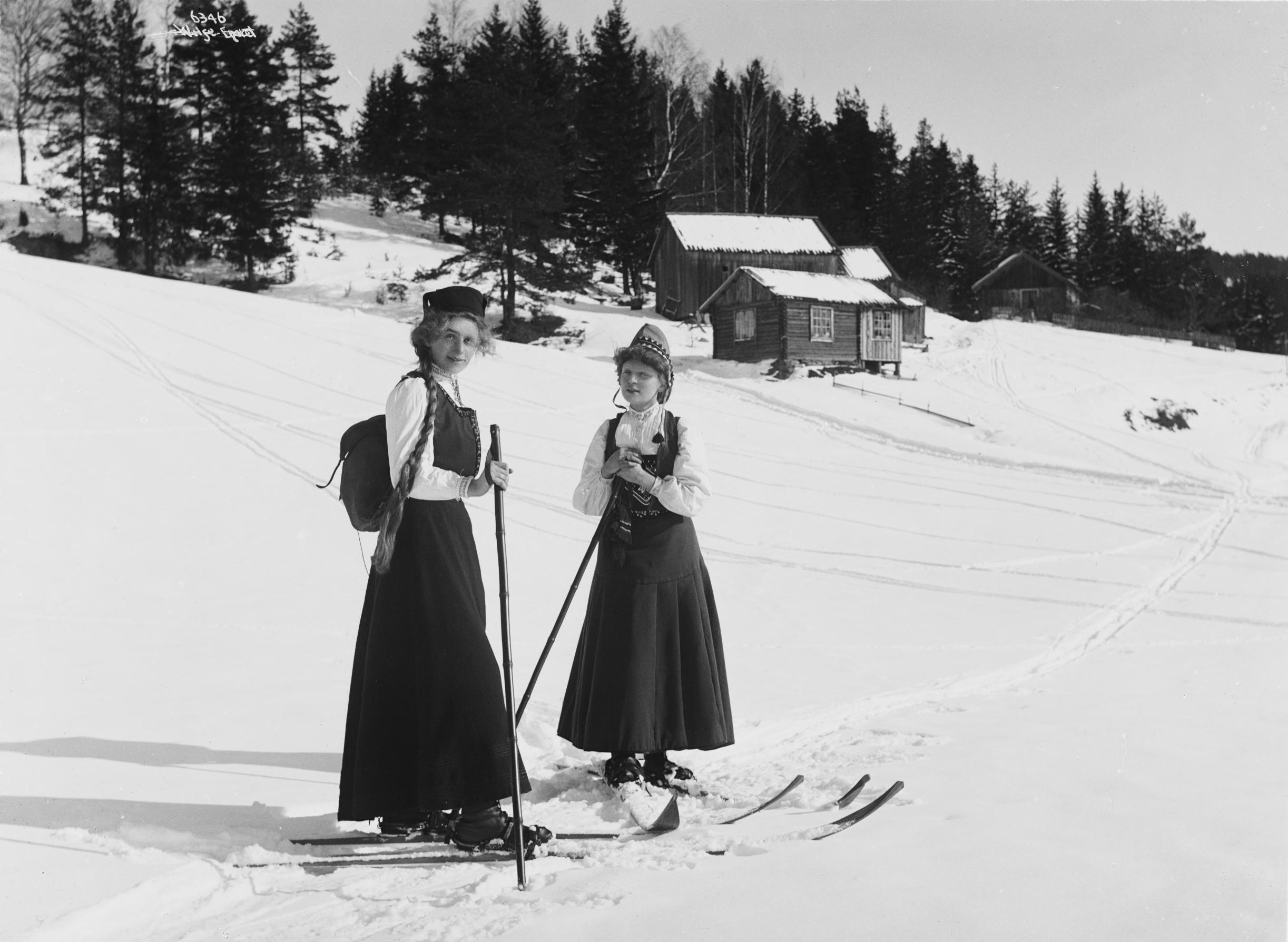 Don't go skiing in your folk costume, like these two postcard ladies in 1907. | Photo: Anders Beer Wilse - Norsk Folkemuseum nb.no cc pdm.