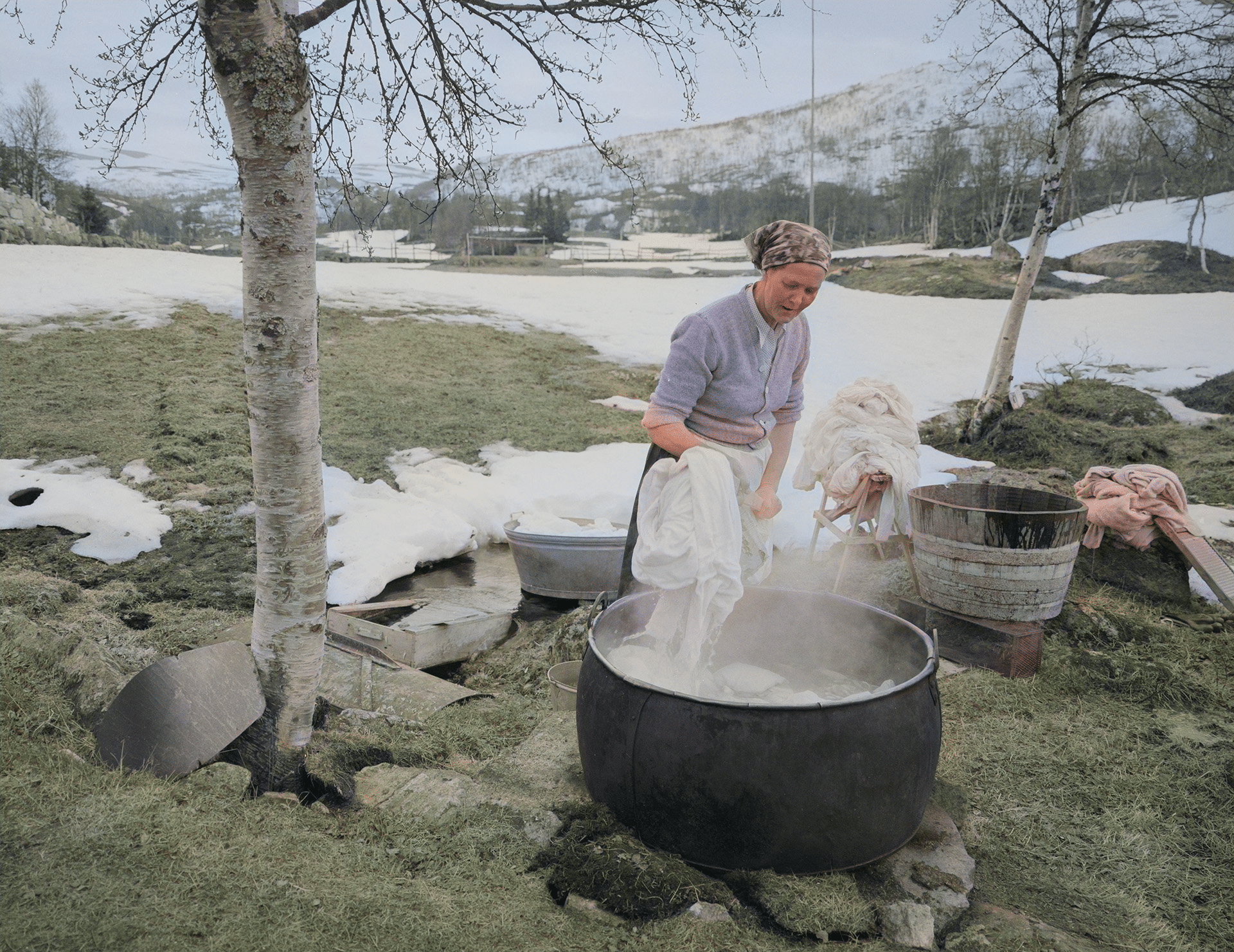 Doing laundry by the creek - in boiling water on the fire. | Photo: Arnulf Husmo - Mittet & Co. AS DeOldify cc pdm.
